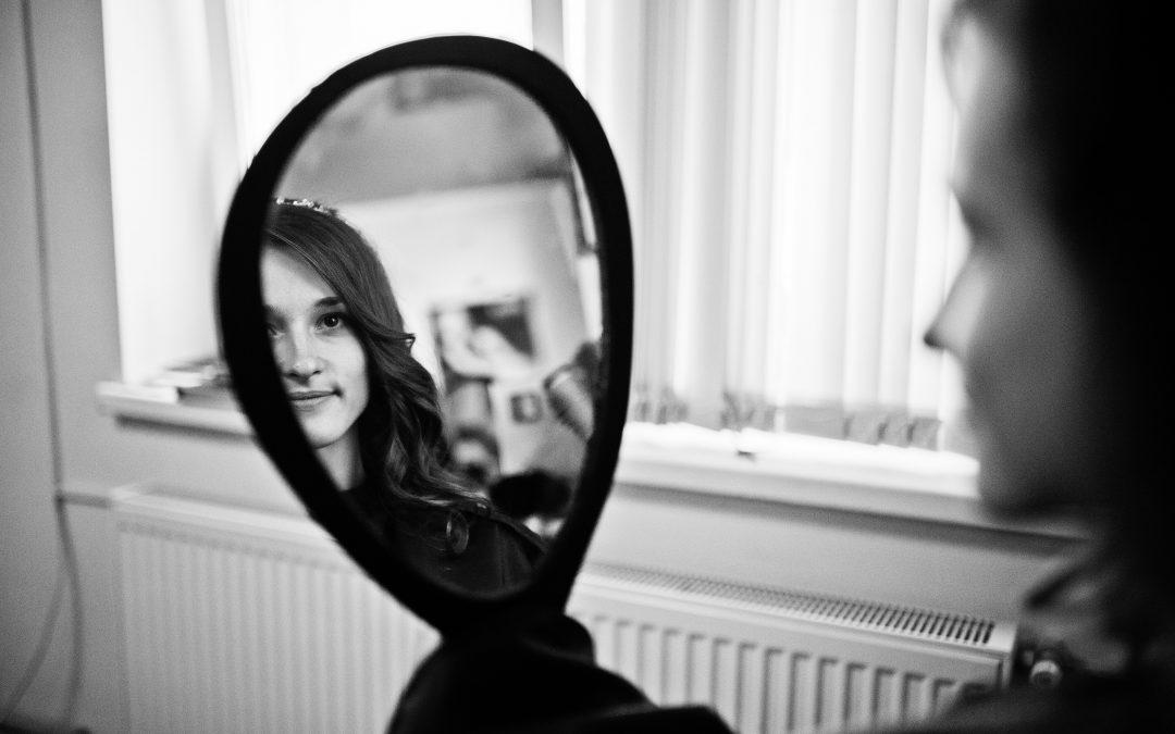 Girl bride looks in the mirror in beauty salon