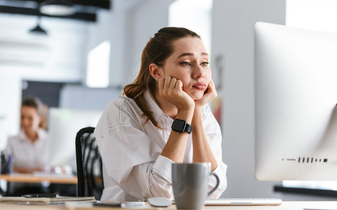 Bored young woman dressed in shirt sitting at her workplace